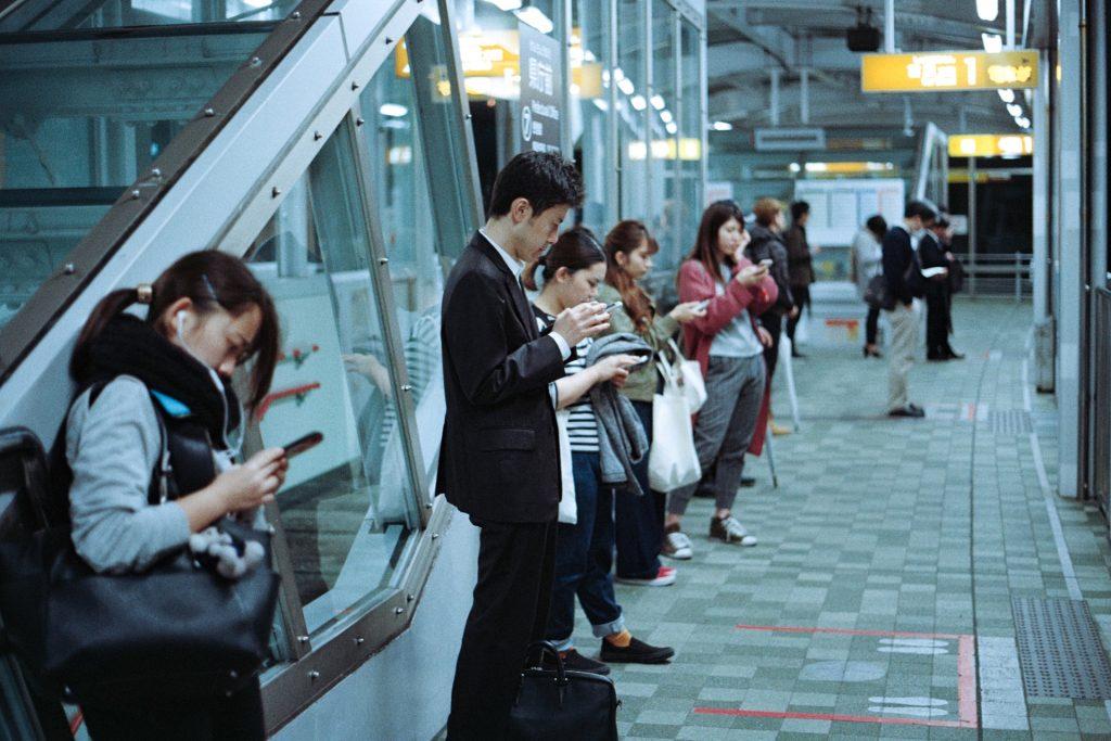 ludzie w komunikacji miejskiej używający smartfonów